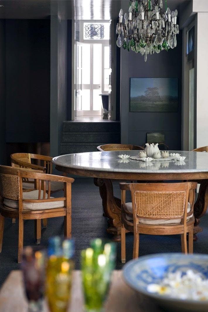 Круглый обеденный стол с деревянными креслами на фоне черных стен кухни фото
