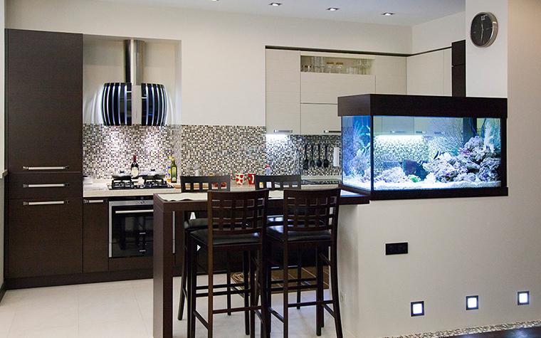 </p> <p>Автор проекта: Анна Савикова. </p> <p>Открытая кухня, соединенная с гостиной большим аквариумом, получила мозаичную отделку с намеком на аква тему. Широкая полоса над рабочей поверхностью кухни облицована разноцветной мозаикой, которая издалека напоминает мелкую морскую гальку. </p> <p>