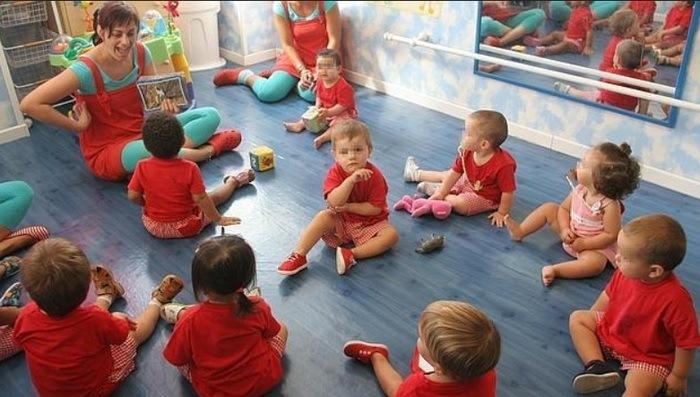 Дети сидят не на стульчиках, а прямо на полу.