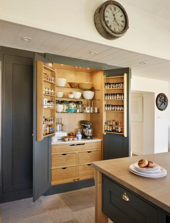 Большой шкаф с подсветкой и множеством полок для хранения специй, сыпучих и других кухонных принадлежностей