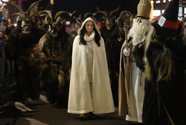 Тем временем Святой Николай вместе с ангелом хвалят хороших детей австрия, крампус, мир, парад, праздник, фото, шествие