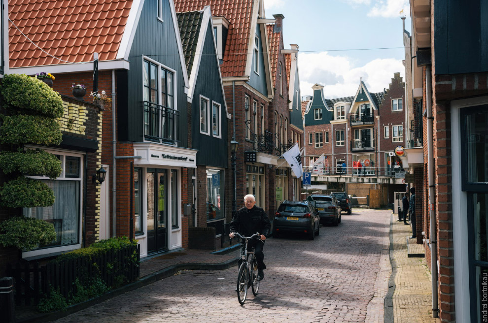 Resident of the village of Volendam by bike in front of the typical traditional houses, Netherlands.
