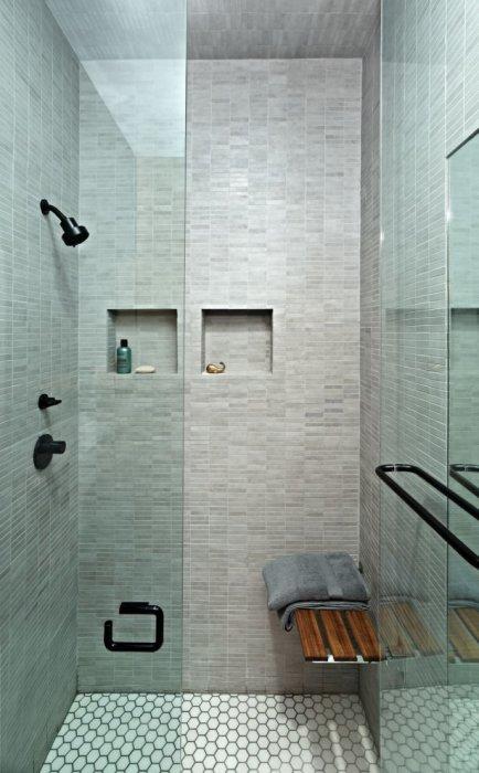 Небольшая ванная комната с душевой кабинкой с прозрачными стенами и керамической плиткой.