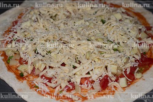 Посыпать пиццу тертым сыром.