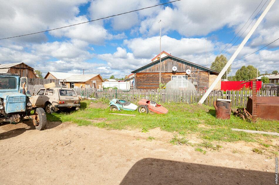 9. Яснэг, транспортные средства у одного из домов.