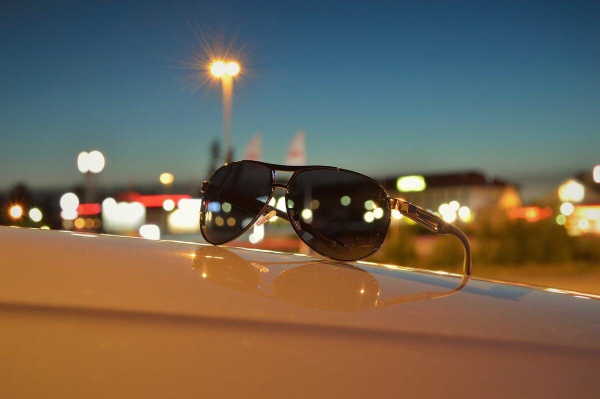 Солнцезащитные очки на фоне вечернего города. /Фото: cdn.pixabay.com