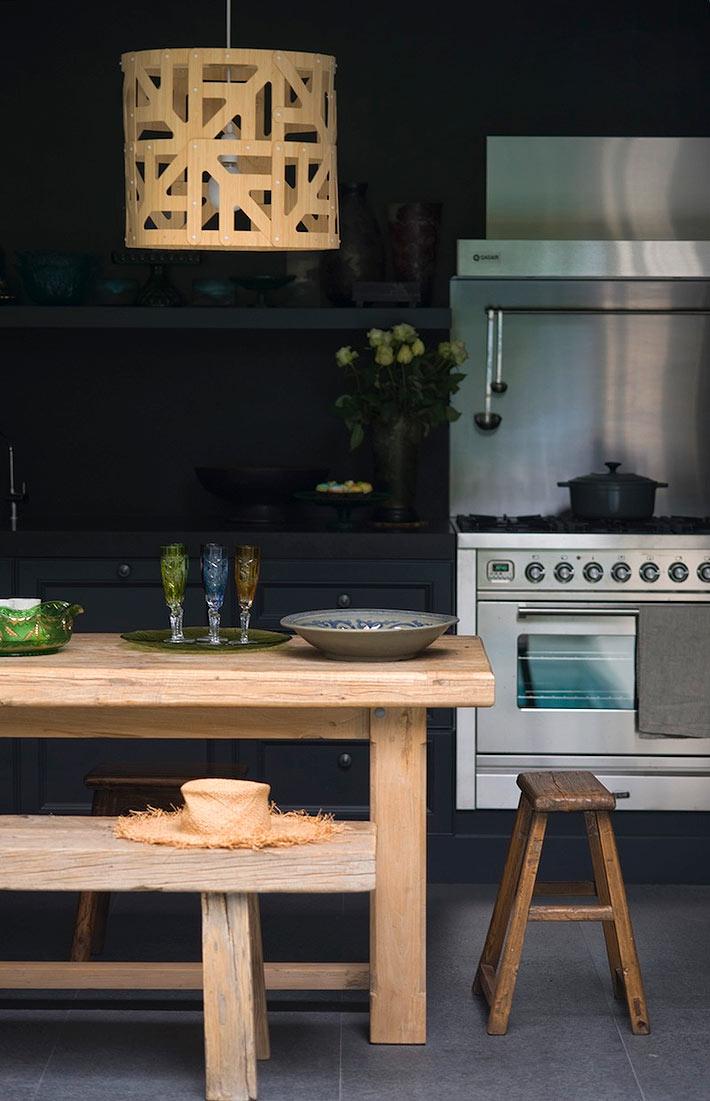 Кухня черного цвета с кухонным столом и люстрой из светлого дерева фото