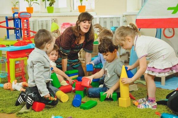 Довольный воспитатель играет с детьми