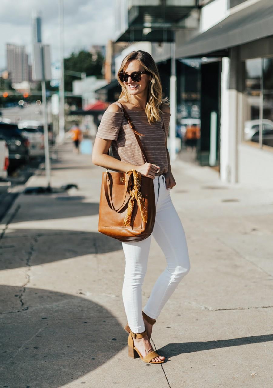 Девушка с большой сумкой и белых джинсах