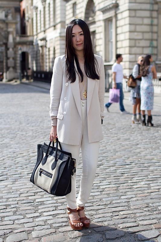 Девушка с большой сумкой и в белом костюме