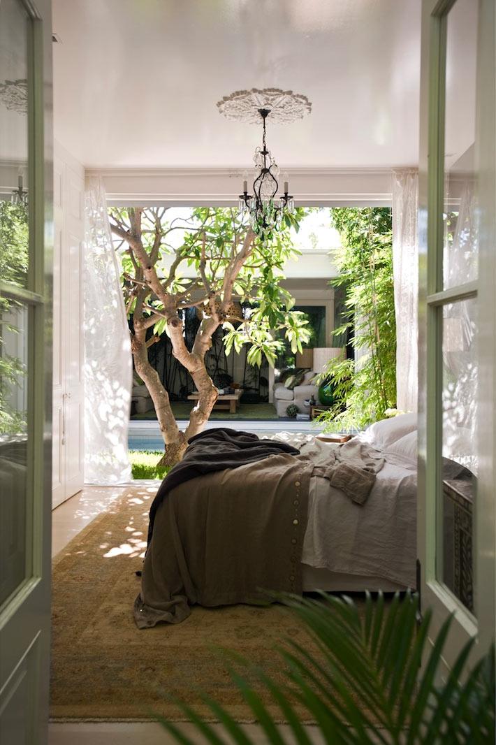 Интерьер спальной комнаты свыходом во внутренний двор с бассейном фото
