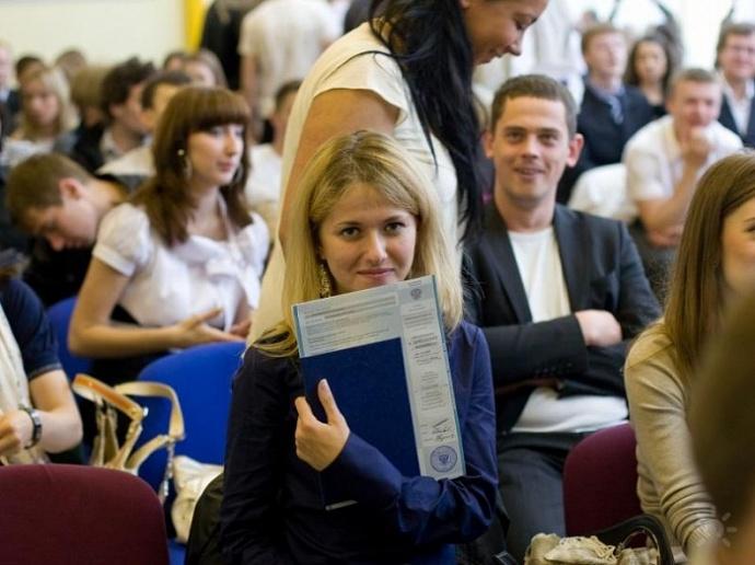 Выпускные экзамены перед дипломом. Длинный стол, за ним комиссия. На столе цветы и билеты…