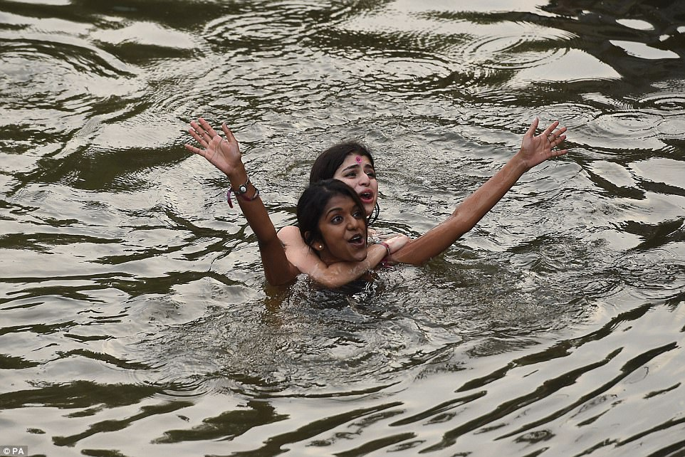 Guests threw out their inhibitions as they cast aside their expensive costumes to cool down in the river this morning