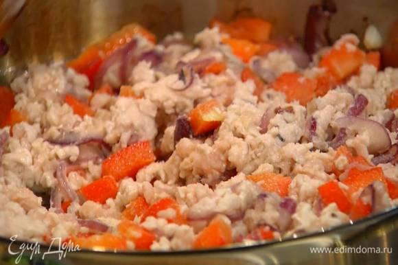 Выложить к овощам куриный фарш, непрерывно перемешивая, разбить лопаткой крупные кусочки и слегка обжарить, затем посолить и поперчить.
