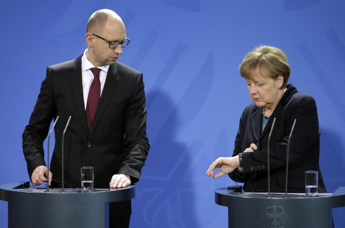 German Chancellor Angela Merkel, right, and the Prime Minister of Ukraine, Arseniy Yatsenyuk, left, look at Merkel's watch during a joint press conference as part of a meeting at the chancellery in Berlin, Germany, Thursday, Jan. 8, 2015. (AP Photo/Michael Sohn)