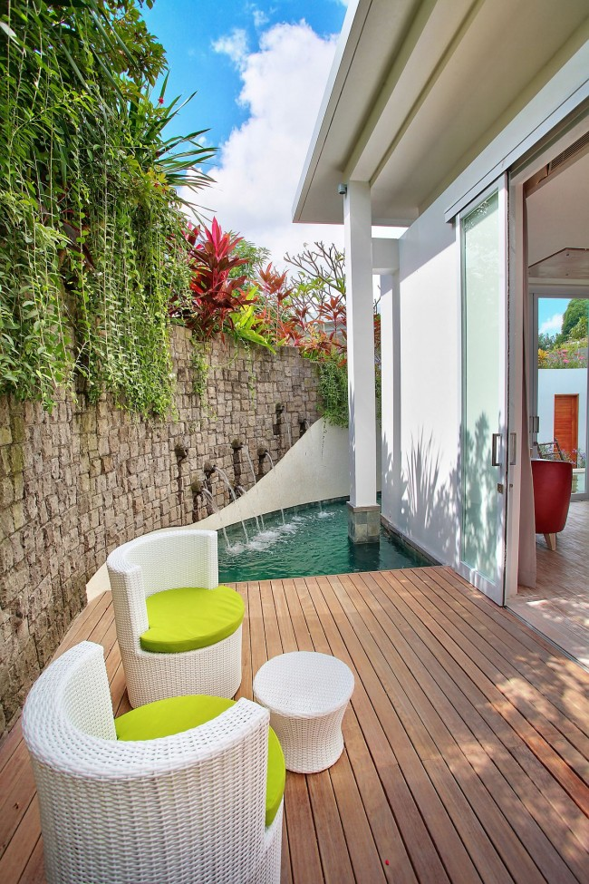 Небольшая терраса, окруженная каменной стеной, защищена от ветра и посторонних взглядов. Обратите внимание на белую плетеную мебель
