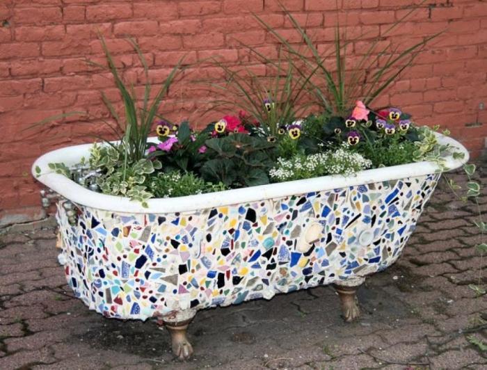 Клумба из старой ванны декорирована битым кафелем.