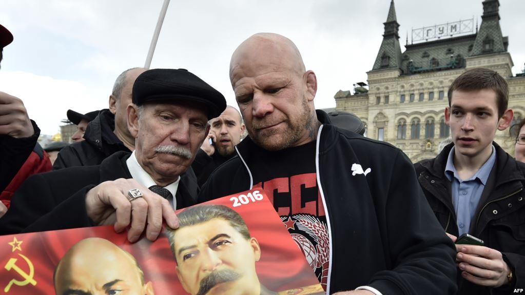 Американский боец Джефф Монсон держит изображение Иосифа Сталина и Владимира Ленина