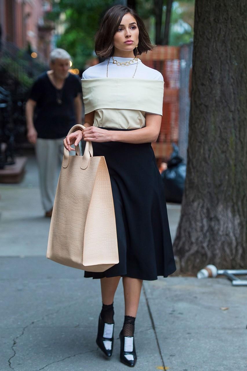 Девушка с большой сумкой и в миди-юбке