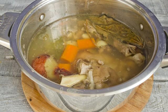 Добавляем чеснок и морковь в кастрюлю за 20 минут до готовности. Остужаем готовый бульон