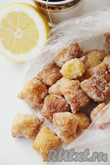 Остывшие лимонные подушечки положить в пакет, посыпать сахарной пудрой и завязать пакет. Равномерно распределить сахарную пудру по печенью.