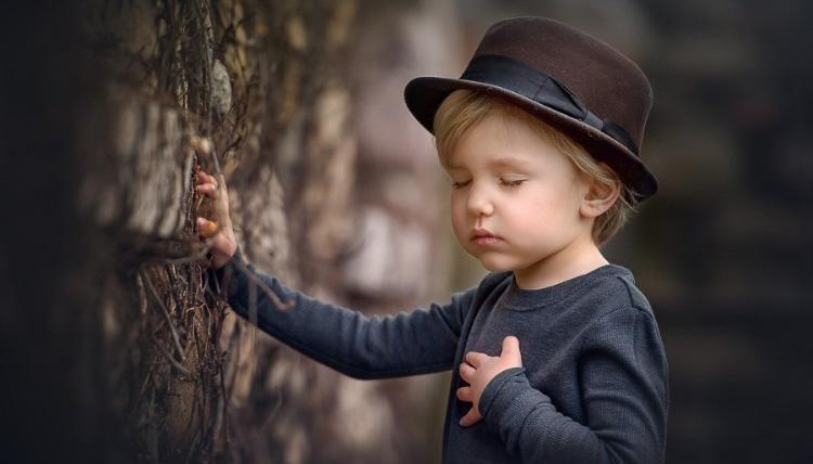 маленький мальчик, закрыв глаза, трогает своё сердечко