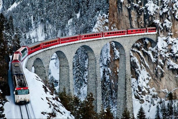 Арочный, каменный одноколейный железнодорожный виадук через реку Ландвассер в Альпах возле населенного пункта Филизур в кантоне Грисонс, Швейцария.