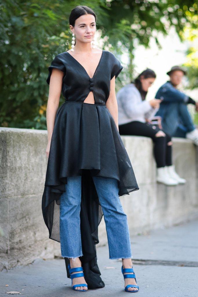 Девушка в джинсах и асимметричном платье