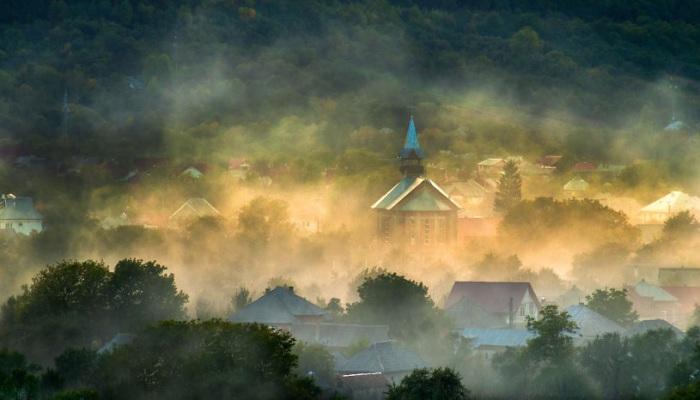 Небольшое поселение в горах, окруженное утренним туманом.