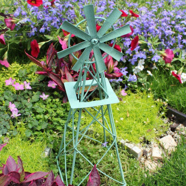 Металлическая декоративная мельница в окружении цветов