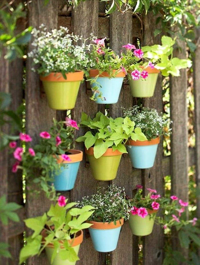 Развесив на небольшом расстоянии между собой горшочки с цветами, можно получить своеобразную живую изгородь