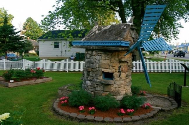 Декоративная мельница, выложенная с камня для хранения садового инвентаря