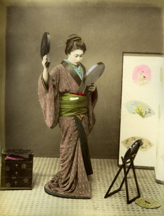 Девушка смотрится в зеркала, оценивая безукоризненность своей прически.