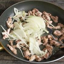 Обжариваем мясо 5-7 минут на сильном огне, затем перемешиваем, добавляем лук
