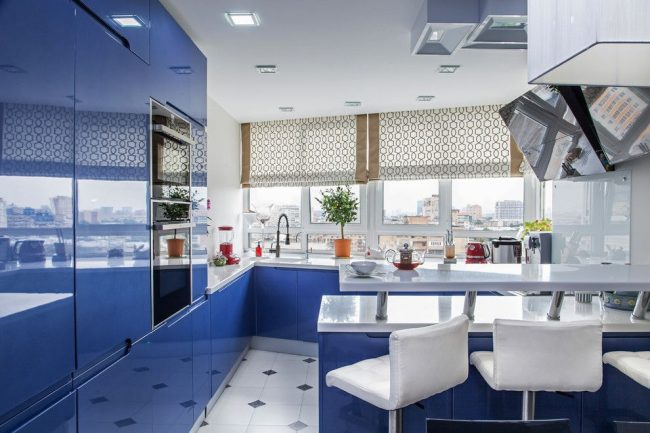 Синяя современная кухня с глянцевыми фасадами и угловой мойкой у окна