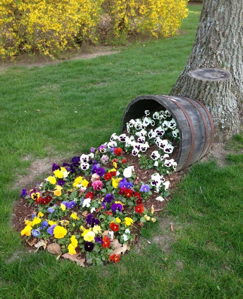 Оригинальное решения клумбы в виде рассыпавшейся из горшка земли с цветами петуний