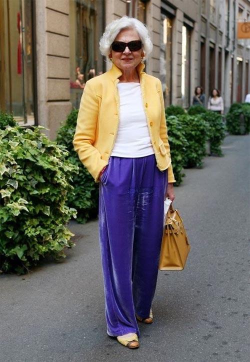 Женщина в возрасте в бархатных брюках и желтом жакете