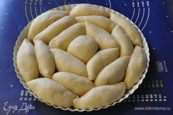 Форму для выпечки (у меня диаметром 28 см) смазать сливочным маслом и выложить пирожки швом вниз, чередуя пирожки с разными начинками. Накрыть форму с пирожками полотенцем и оставить подходить на 15-20 минут. Включить разогреваться духовку до 180°C.