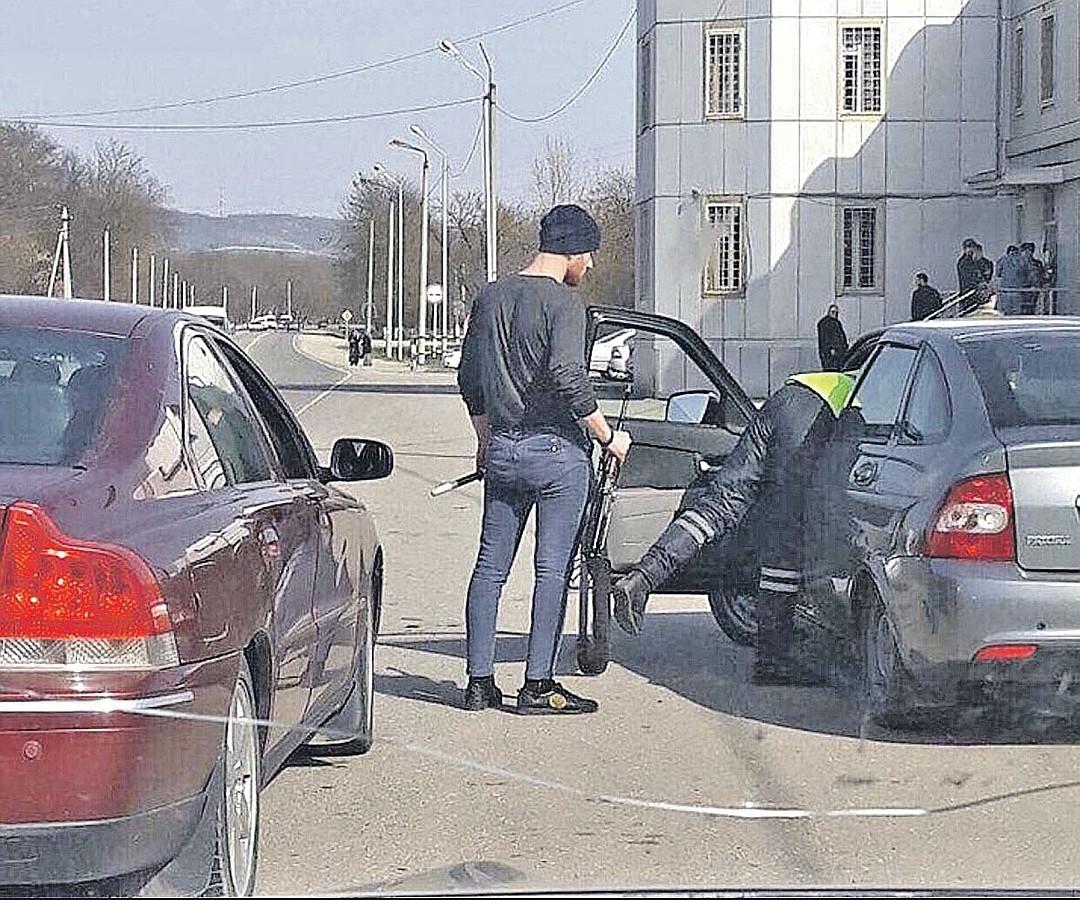 Этот шедевральный кадр разлетелся по соцсетям в начале весны. Инспектор осматривает машину, дав подержать водителю свои жезл и калаш. По-братски, по-кавказски! Фото: youtube.com