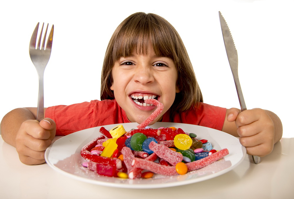 cute European female child smiling happy eating candy like crazy with fork and knife in sugar abuse , unhealthy sweet nutrition concept , children candy addiction and kids dental care