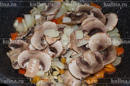 Чеснок нарезать и выложить к грибам.