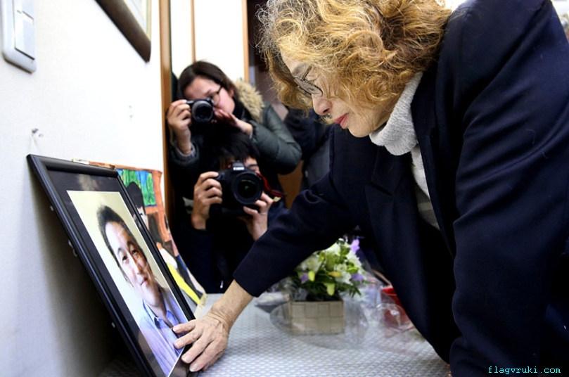 На фото: мать покойного Джанко Ишидо смотрит на портрет своего сына после подтверждения его смерти.