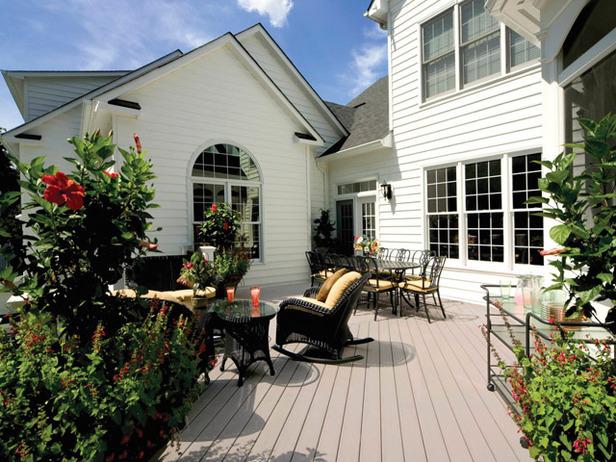 Composite deck with black wicker furniture, flowers and plants, white home exterior, and windows.