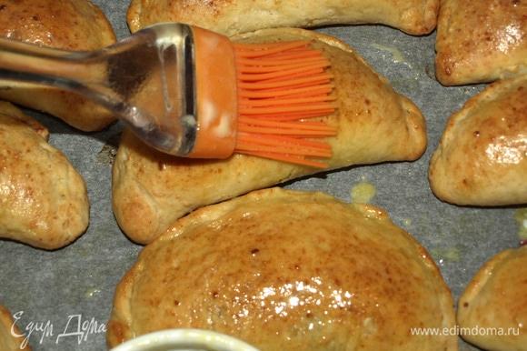 Достаем готовые пирожки и горячими смазываем сливочным маслом.
