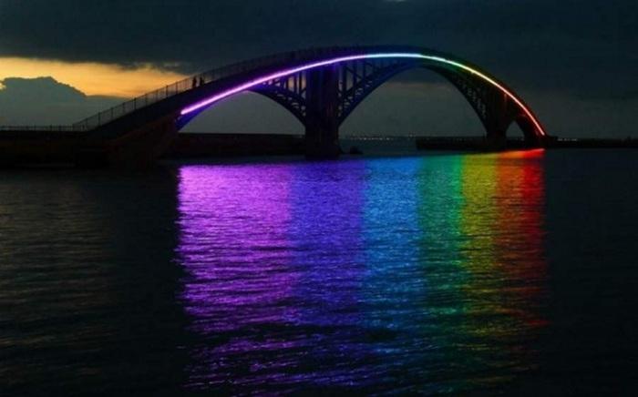 Конструкция представляет собой висячий мост, который полностью освещается всеми цветами радуги.