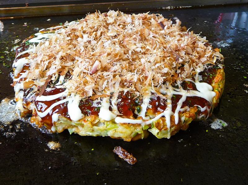 Окономияки — одно из популярнейших блюд японской уличной кухни. Это — жареная лепешка из смеси разнообразных ингредиентов, смазанная специальным соусом и посыпанная очень тонко нарезанным сушеным тунцом еда, япония
