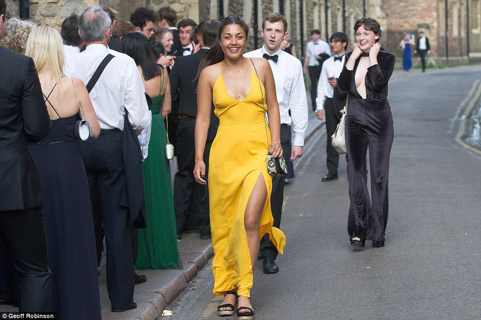 Stopping traffic: A female reveller kicks off the night in style in a show-stopping yellow gown as she joins the queue to get in