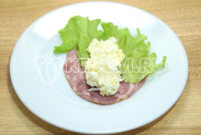 На ломтик ветчины выложить небольшой листик салата и сырную начинку.