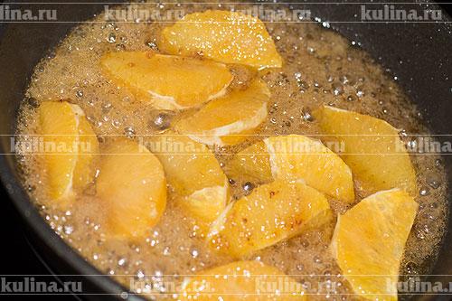 Апельсин очистить, нарезать, выложить в карамель и прогреть 1 минуту.
