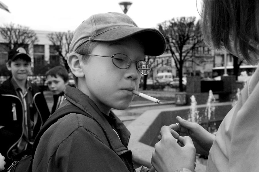 Мальчик с сигаретой прикуривает